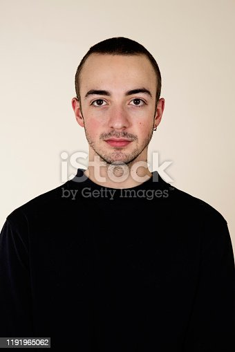 Portrait of millennial young man with close shaved hair. He is looking in the camera without a smile. He is wearing a black t-shirt. Beige background. Vertical waist up studio shot with copy space.
