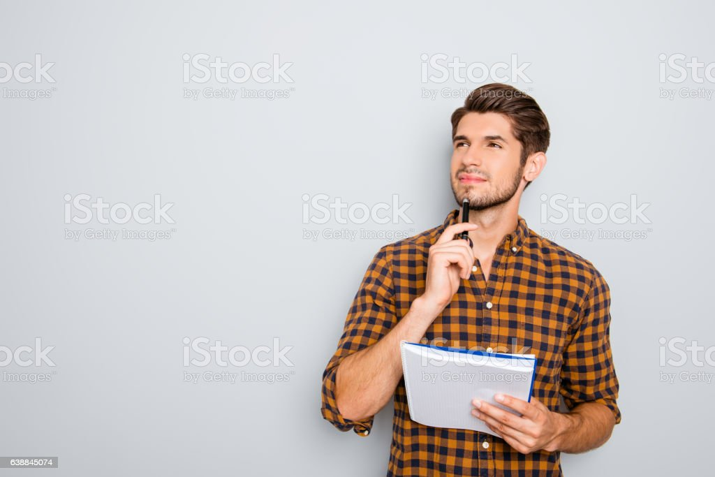 Portrait of minded man with notebook isolated on gray background stock photo