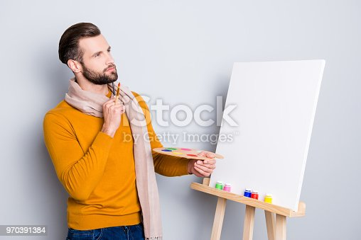 636761588istockphoto Portrait of minded ponder artist having brushes and palette in arms holding hand near chin, imagine future picture, isolated on grey background 970391384