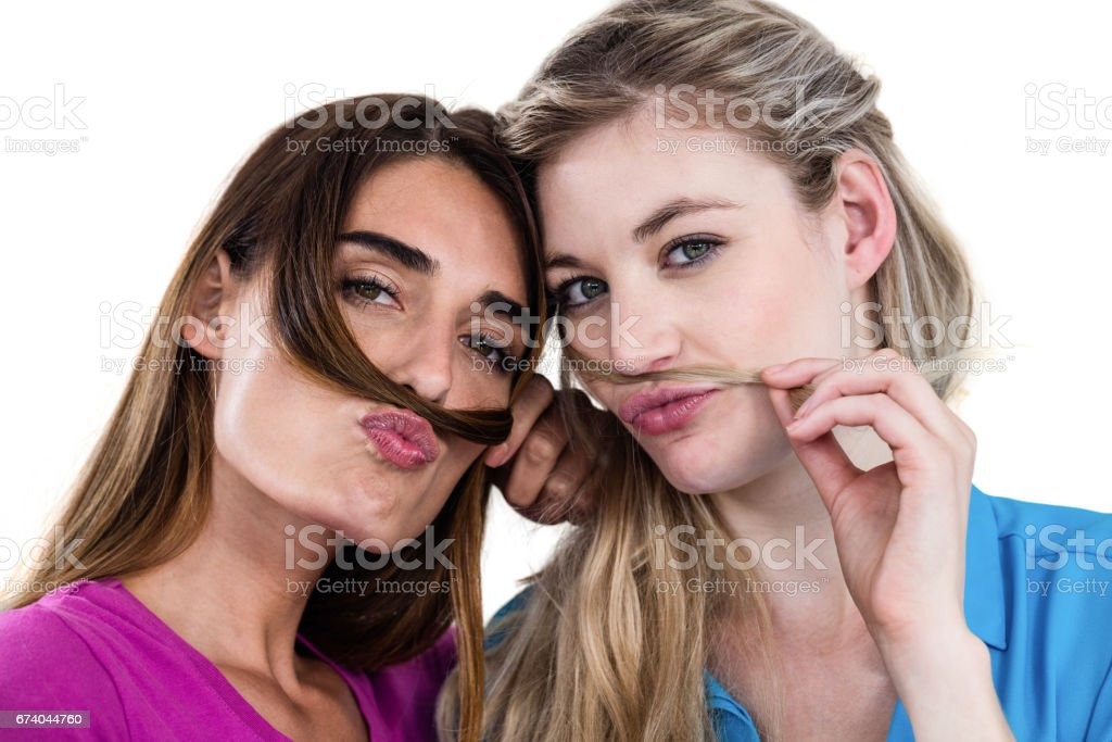 Portrait of mischievous friends playing with hair royalty-free stock photo