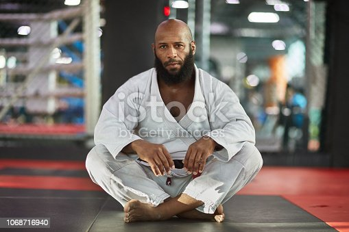 1069872470istockphoto Portrait of mixed martial artist sitting at gym 1068716940