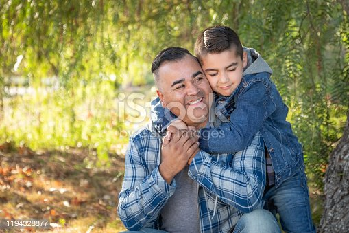 Portrait of Mixed Race Father And Son Having Fun Outdoors.