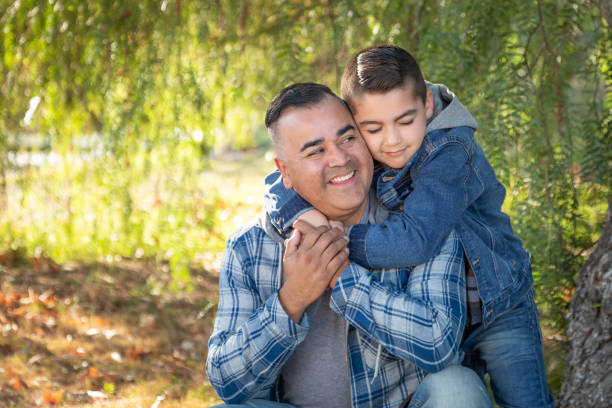 Portrait of Mixed Race Father And Son Having Fun Outdoors stock photo