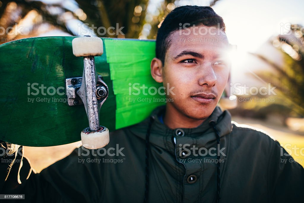 Portrait of Mixed Race Person Holding Skateboard Behind Head stock photo