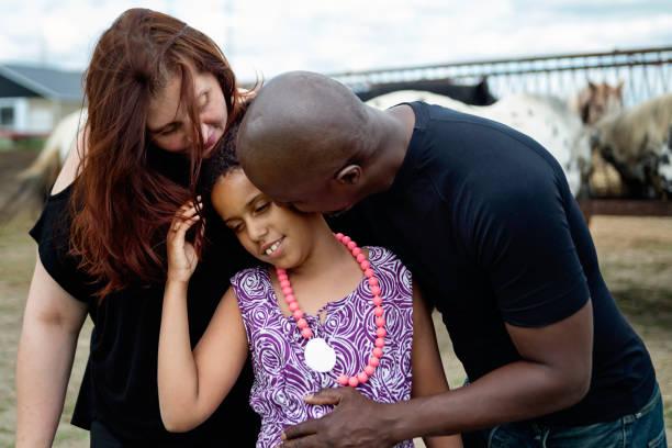 porträt der gemischten rassenfamilie mit autisttochter mit pferden. - autismus stock-fotos und bilder