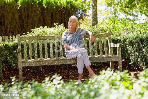 istock Portrait of modern, attractive mature woman sitting in the park 668063890