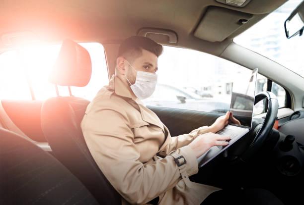 Porträt des modernen bärtigen Mannes auf der Straße. Lifestyle-Konzept mit Kopierraum. Er drinnen das Auto, mit medizinischer Gesichtsmaske und arbeiten mit Laptop – Foto