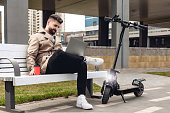Portrait of modern bearded man at the street. Lifestyle concept with copy space. He is working with personal computer near electric kick scooter