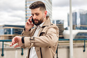 Portrait of modern bearded man at the street. Lifestyle concept with copy space. He is calling on mobile phone and checking the time on smart watch