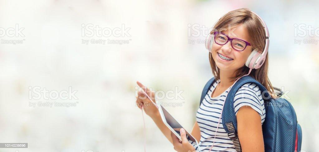 Porträt des modernen glücklich Teen Schulmädchen mit Zahnspangen Brillen Tasche Rucksack Kopfhörer und Tablet. Lizenzfreies stock-foto