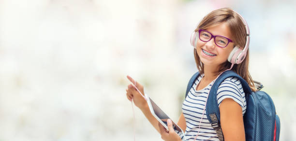 Portrait of modern happy teen school girl with dental braces glasses bag backpack headphones and tablet. stock photo