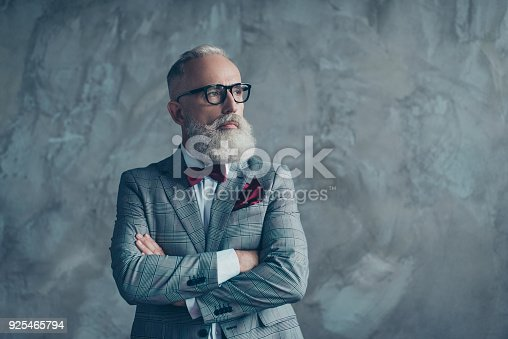 Portrait of modern luxurious trendy wealthy intelligent dreamy pensive stylish authoritative clever man wearing checkered grey jacket chic maroon bow-tie imagine smth, isolated on concrete background
