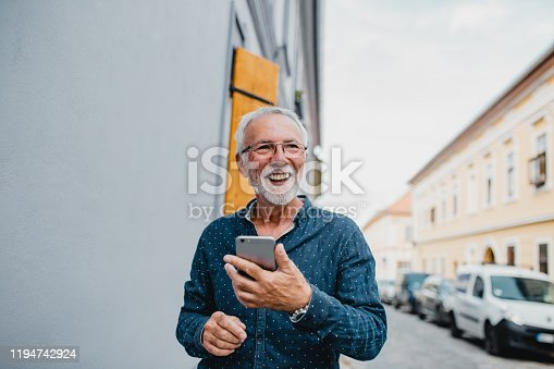 Modern senior men in is standing on the street and he is smiling and holding a smartphone  and smiling