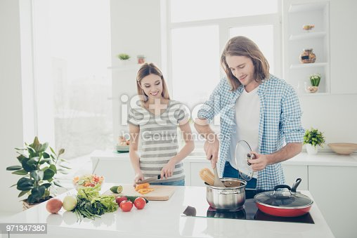 Portrait of modern trendy couple preparing supper together, charming girl cutting fresh vegetables for salad, handsome man boil macaroni on stove. Weekend vacation holiday concept