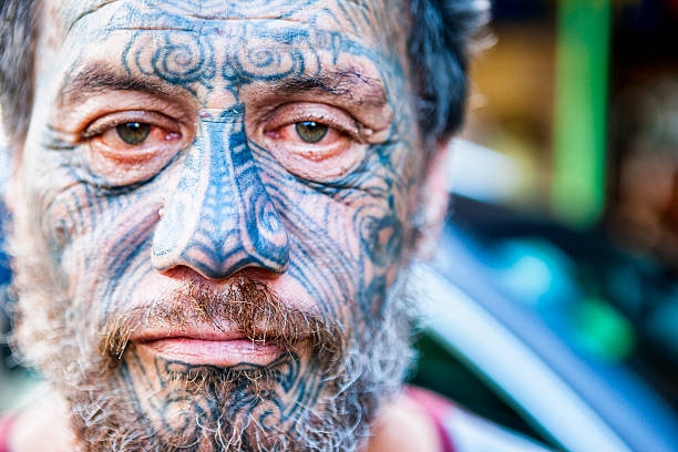 portrait of māori man with traditional tā moko face tattoos - tribal tattoos stock-fotos und bilder
