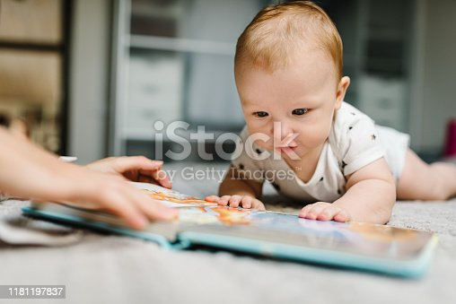 Portrait of mother and baby boy read book in bed at home. Mom with son.
