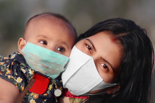 Portrait of Mother and baby daughter covering face with pollution mask against COVID-19 or Coronavirus stock photo