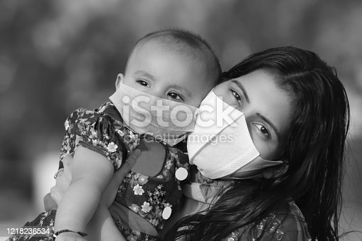 Portrait of Mother and daughter covering face with pollution mask for protection against Coronavirus or COVID-19, New Delhi, India.