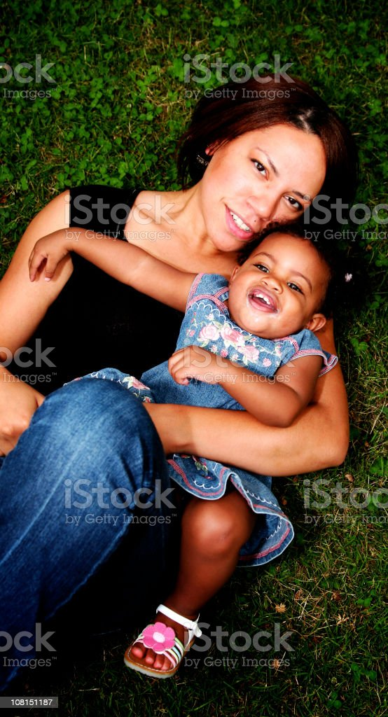Portrait of Mother and Baby Daughter Lying in Grass royalty-free stock photo