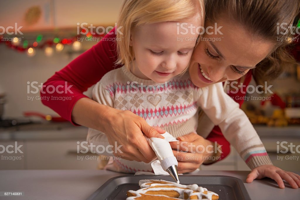 Portrait of mother and baby making christmas cookies in kitchen stock photo