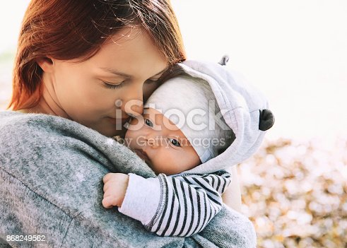 istock Portrait of mother and baby. Sleeping newborn baby in the hands of his mother. 868249562