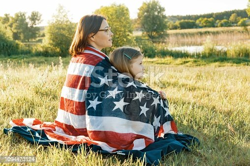 istock Portrait of mother and child daughter with American flag. Looking at natural rural landscape,view from the back 1094473124