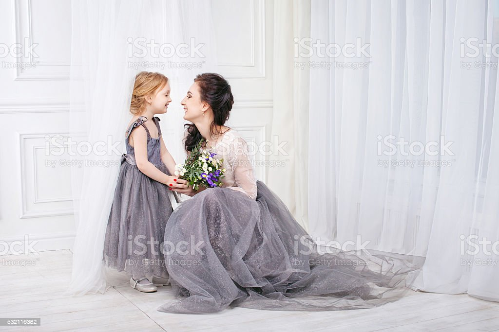 Portrait of mother and daughter in identical dresses.Family look. stock photo