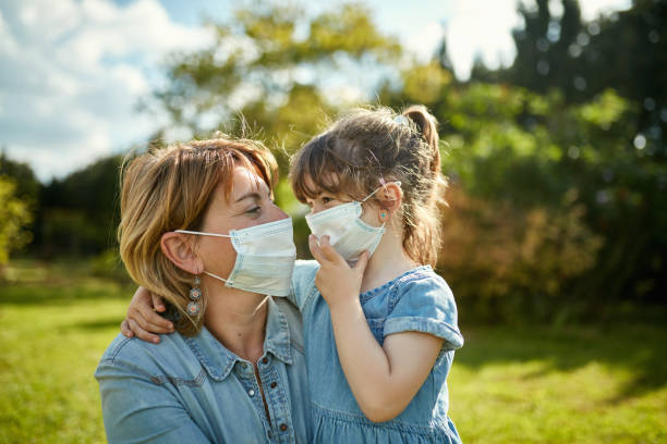 Portrait of Mother and Daughter in Protective Face Masks stock photo