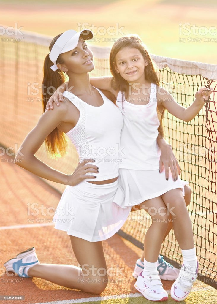 portrait of mother and daughter on the tennis court royalty-free stock photo