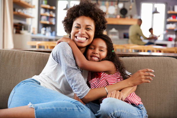 Portrait Of Mother And Daughter Sitting On Sofa Laughing stock photo