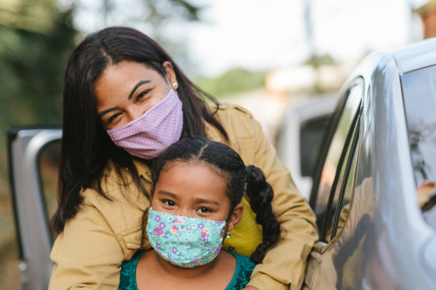 verticale de mère et de descendant utilisant le masque protecteur dans la rue - masque enfant photos et images de collection