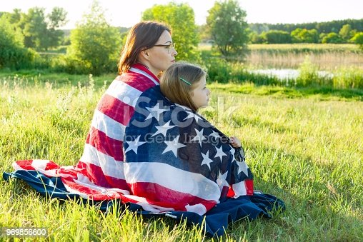 istock Portrait of mother and daughter with American flag. Look at the natural rural landscape,view from the back 969856600