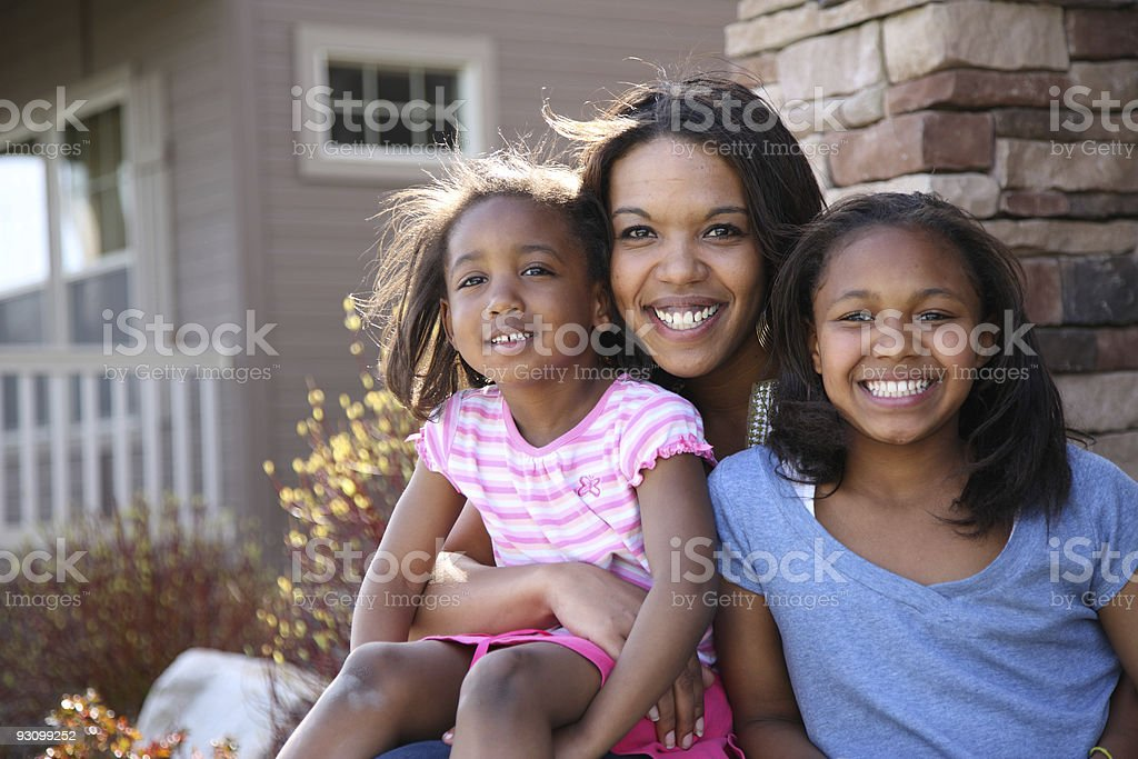 Portrait of mother and daughters sitting on porch stock photo