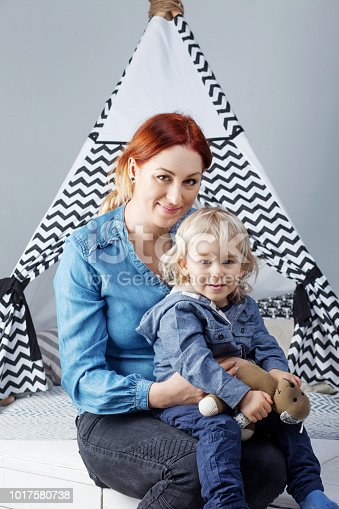 609058672 istock photo Portrait of mother and son against the background of a children's wigwam 1017580738