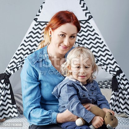 609058672 istock photo Portrait of mother and son against the background of a children's wigwam 1043190656