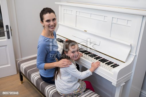 istock Portrait of mother assisting daughter in playing piano 869795946