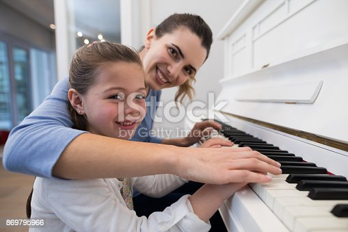 istock Portrait of mother assisting daughter in playing piano 869795966