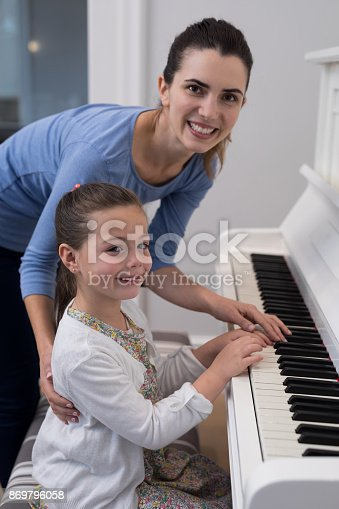 istock Portrait of mother assisting daughter in playing piano 869796058