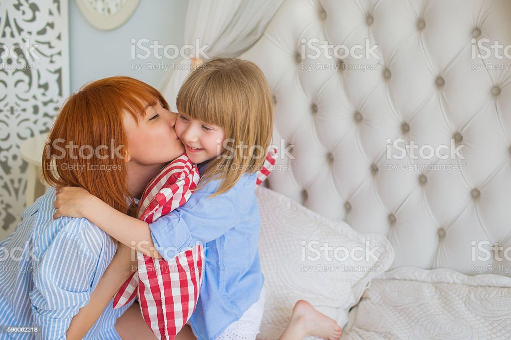 Portrait of mother kisses her little daughter in the morning royalty-free stock photo