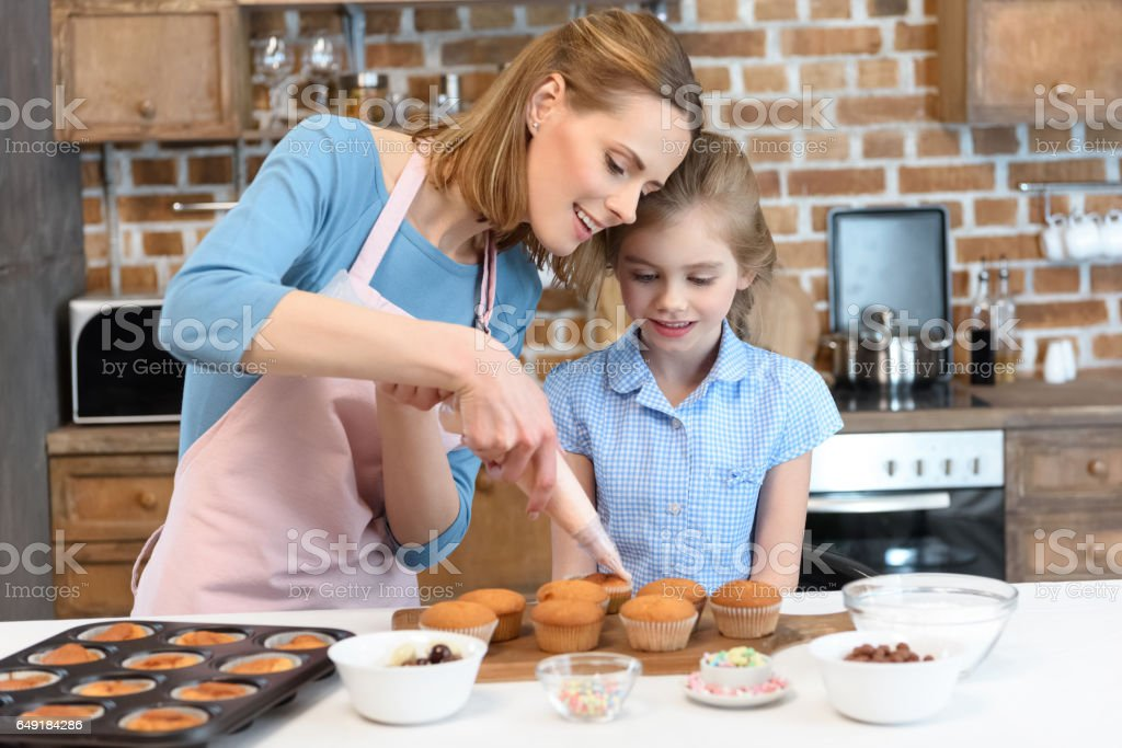 portrait of mother putting cream on cupcakes with daughter portrait of mother putting cream on cupcakes with daughter near by Adult Stock Photo