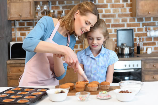 portrait of mother putting cream on cupcakes with daughter portrait of mother putting cream on cupcakes with daughter near by decorating a cake stock pictures, royalty-free photos & images