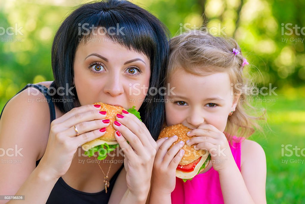 portrait of mother with her daughter with burgers stock photo