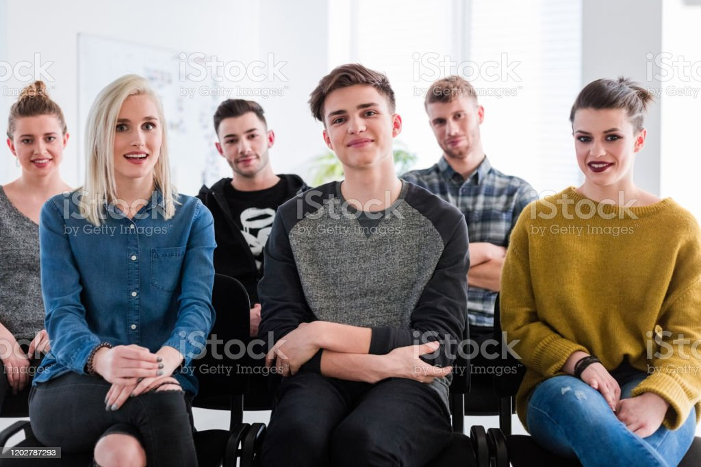 Portrait of motivated friends listening in therapy Portrait of smiling friends sitting at lecture hall. Male and female students are listening in group therapy. They are motivated. 18-19 Years Stock Photo