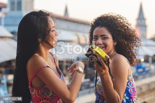 Portrait of multi ethnic friends with a vintage camera enjoying together. Young brazilian women. Famous