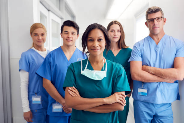 Portrait Of Multi-Cultural Medical Team Standing In Hospital Corridor Portrait Of Multi-Cultural Medical Team Standing In Hospital Corridor nurses stock pictures, royalty-free photos & images