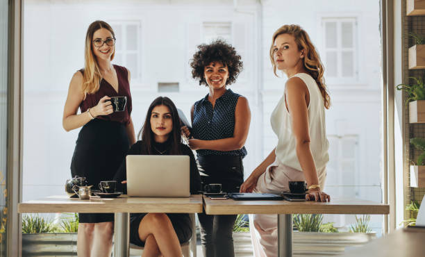Portrait of multi-ethnic businesswomen together Portrait of four successful young businesswomen together in office. Group of multi-ethnic businesswomen looking at camera. jacoblund stock pictures, royalty-free photos & images
