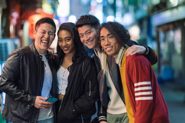 porträt der multiethnischen gruppe von freunden in der straße in der nacht - jamaikanische party stock-fotos und bilder
