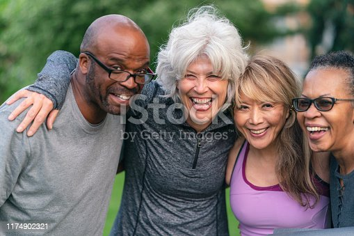 Portrait of a multi-ethnic group of senior friends at a park. The individuals are standing with arms around each others shoulders. They are smiling confidently directly at the camera. They are wearing casual athletic clothing.