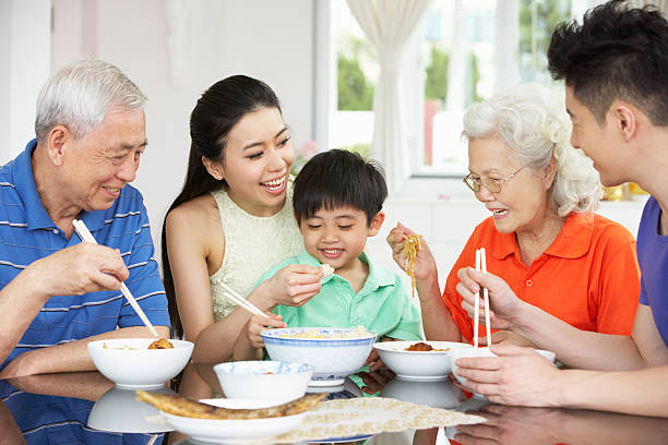 Portrait Of Multi-Generation Chinese Family Eating Meal Together stock photo