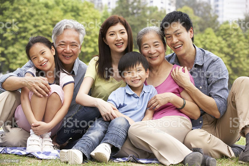 Portrait Of Multi-Generation Chinese Family Relaxing In Park stock photo